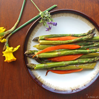 Roasted asparagus and carrots on a plate with spring flowers