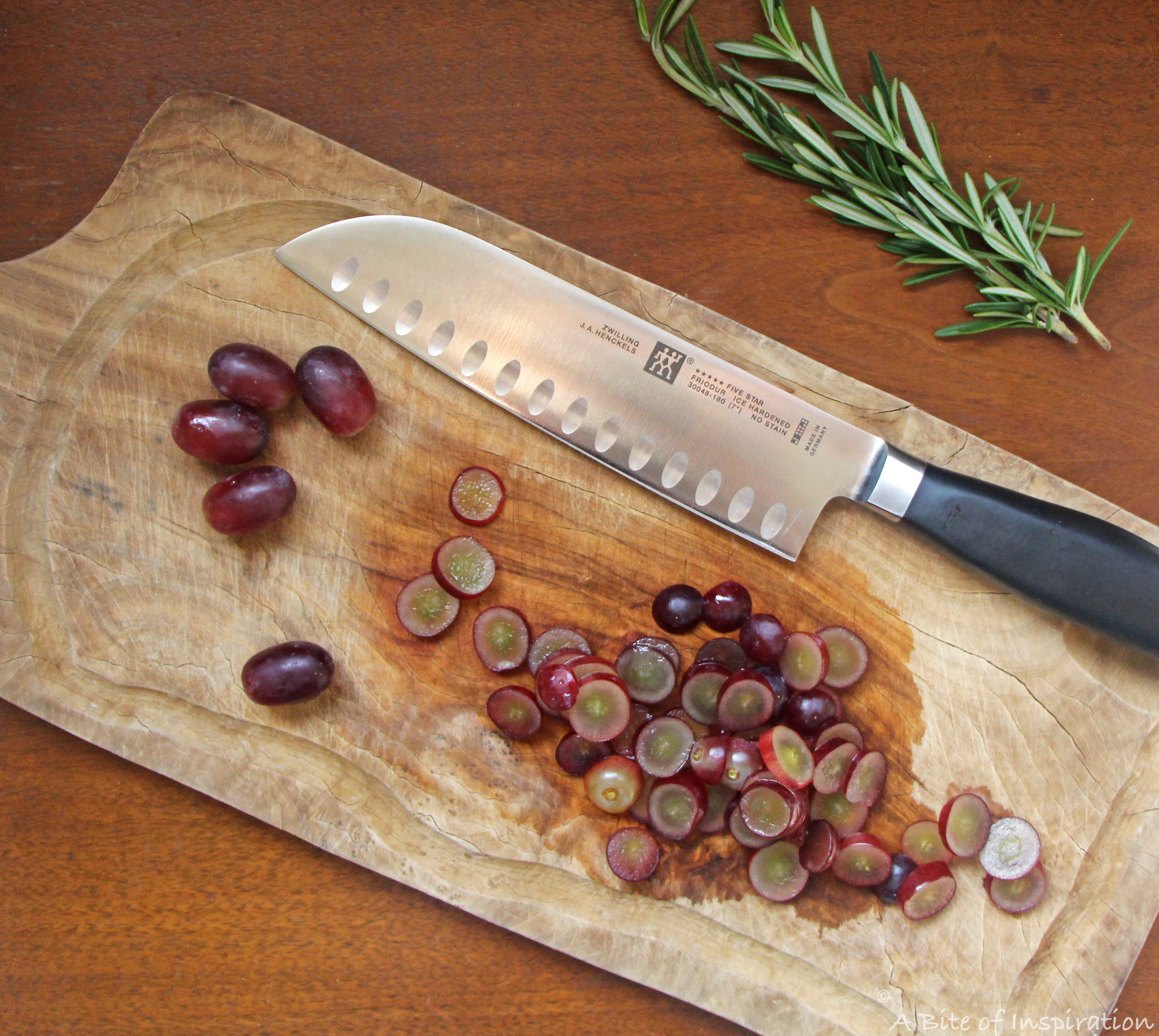 Sliced red grapes on a wooden cutting board ready for pickling with a sprig of fresh rosemary on the side