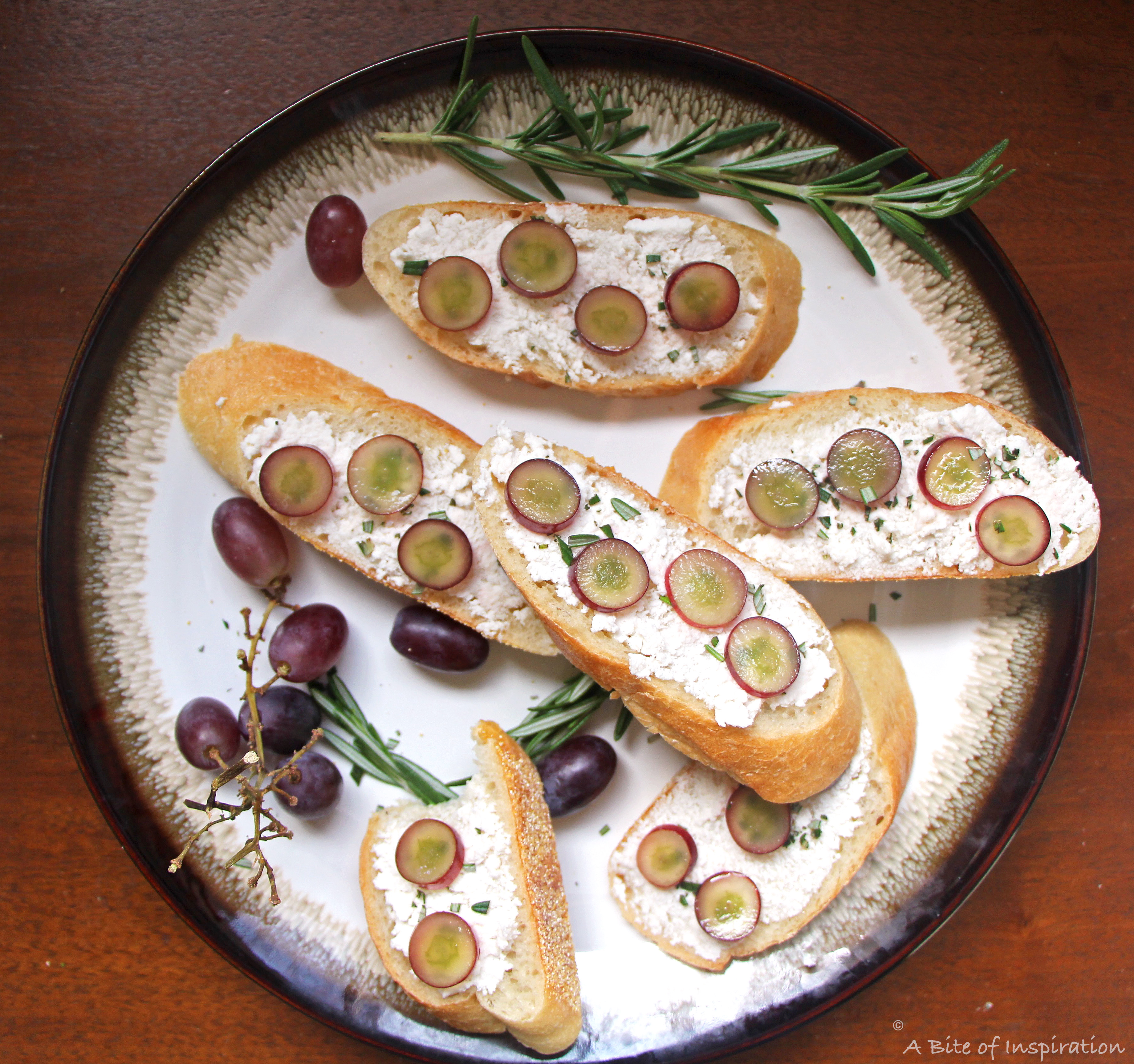 Plate of Soft Cheese Crostini with Pickled Grapes and Rosemary with grapes and sprigs of rosemary around the sides
