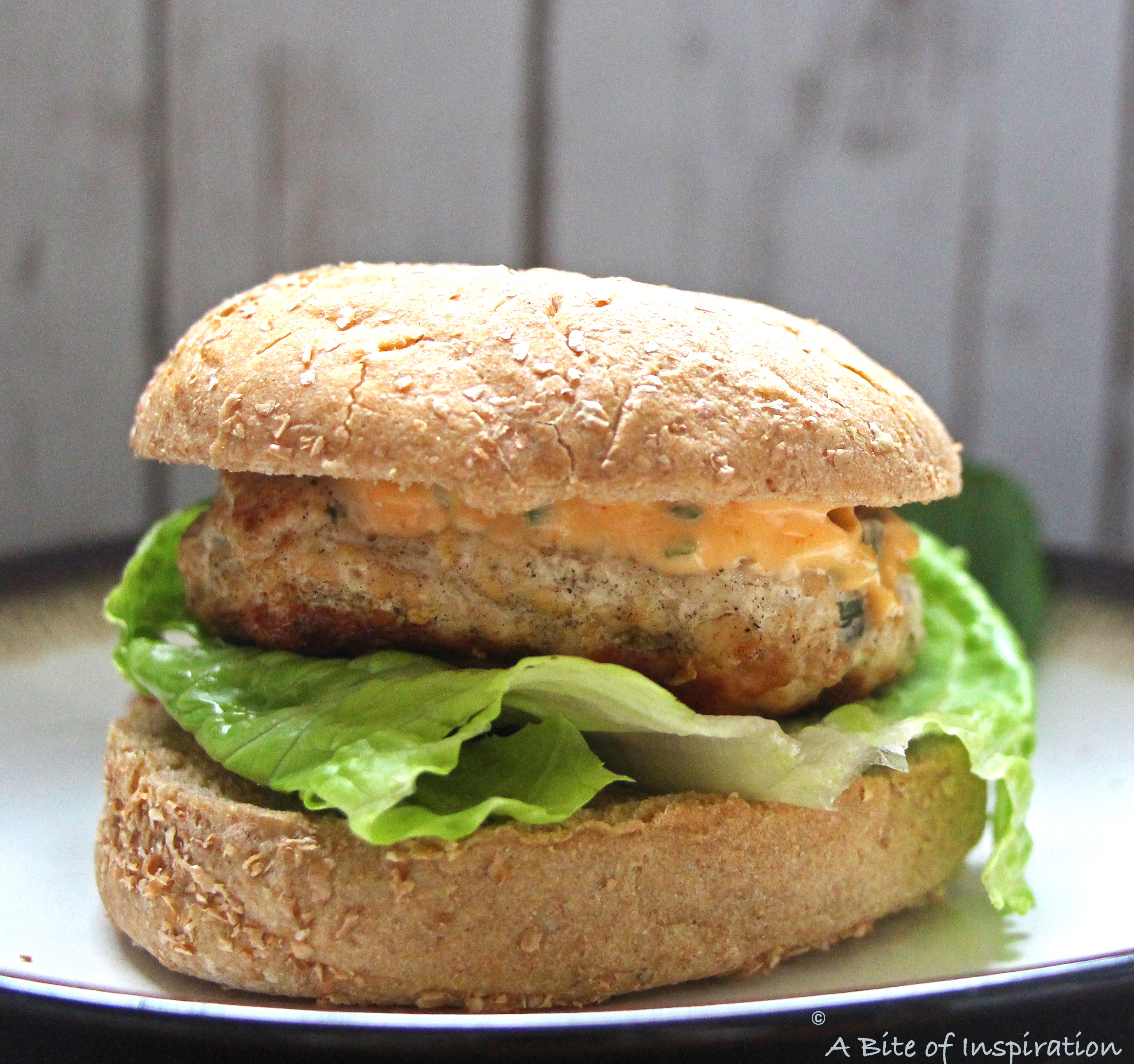 Close up photo of the Thai-Style Chicken Burger with Sriracha Sesame Mayo and romaine lettuce