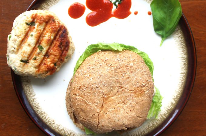 Thai-Style Chicken Burger with Sriracha Mayo on a plate with an extra burger patty and sriracha on the side