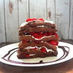 Chocolate cake waffles stacked high with whipped cream and cherries