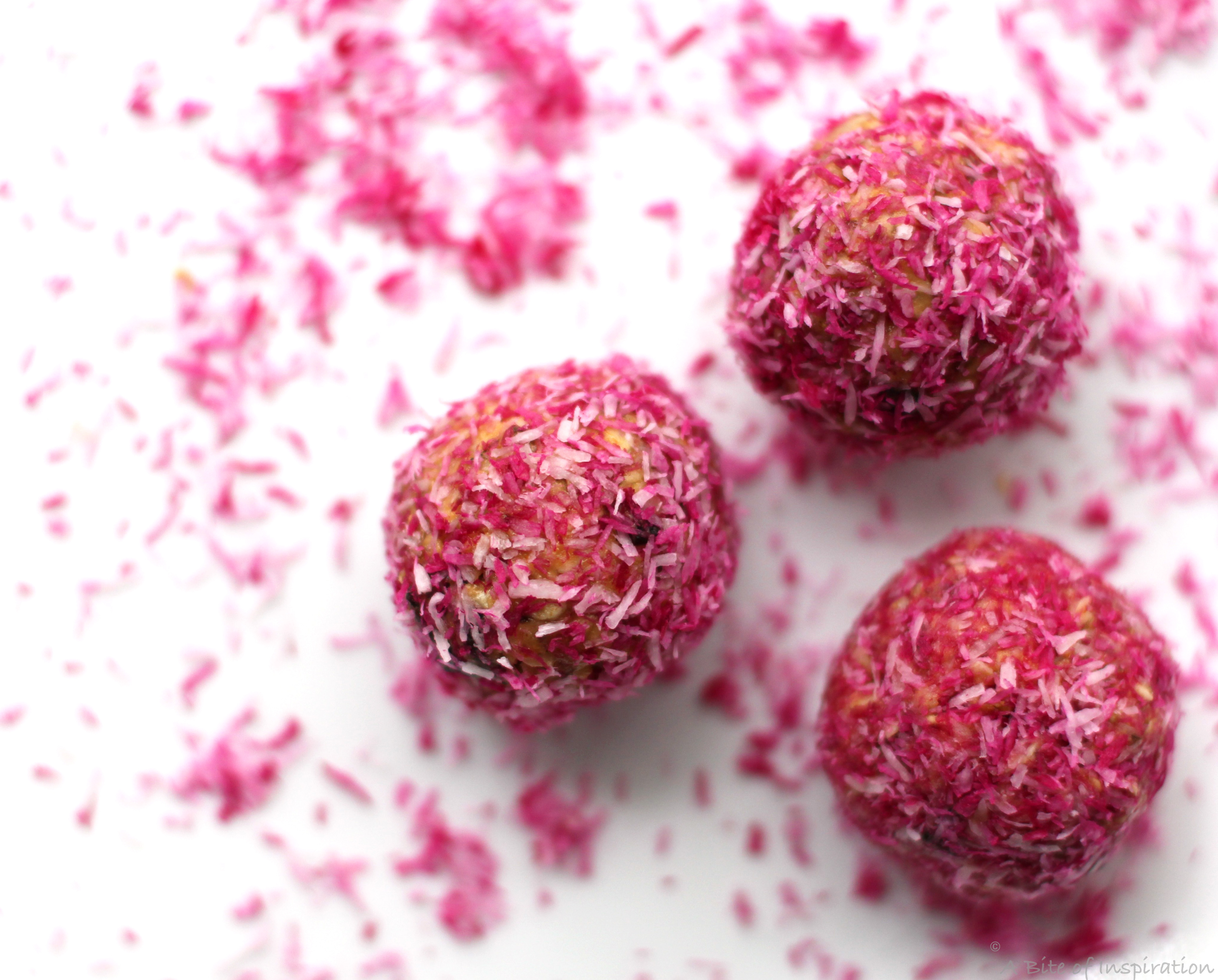 Three pink protein balls with pink shredded coconut
