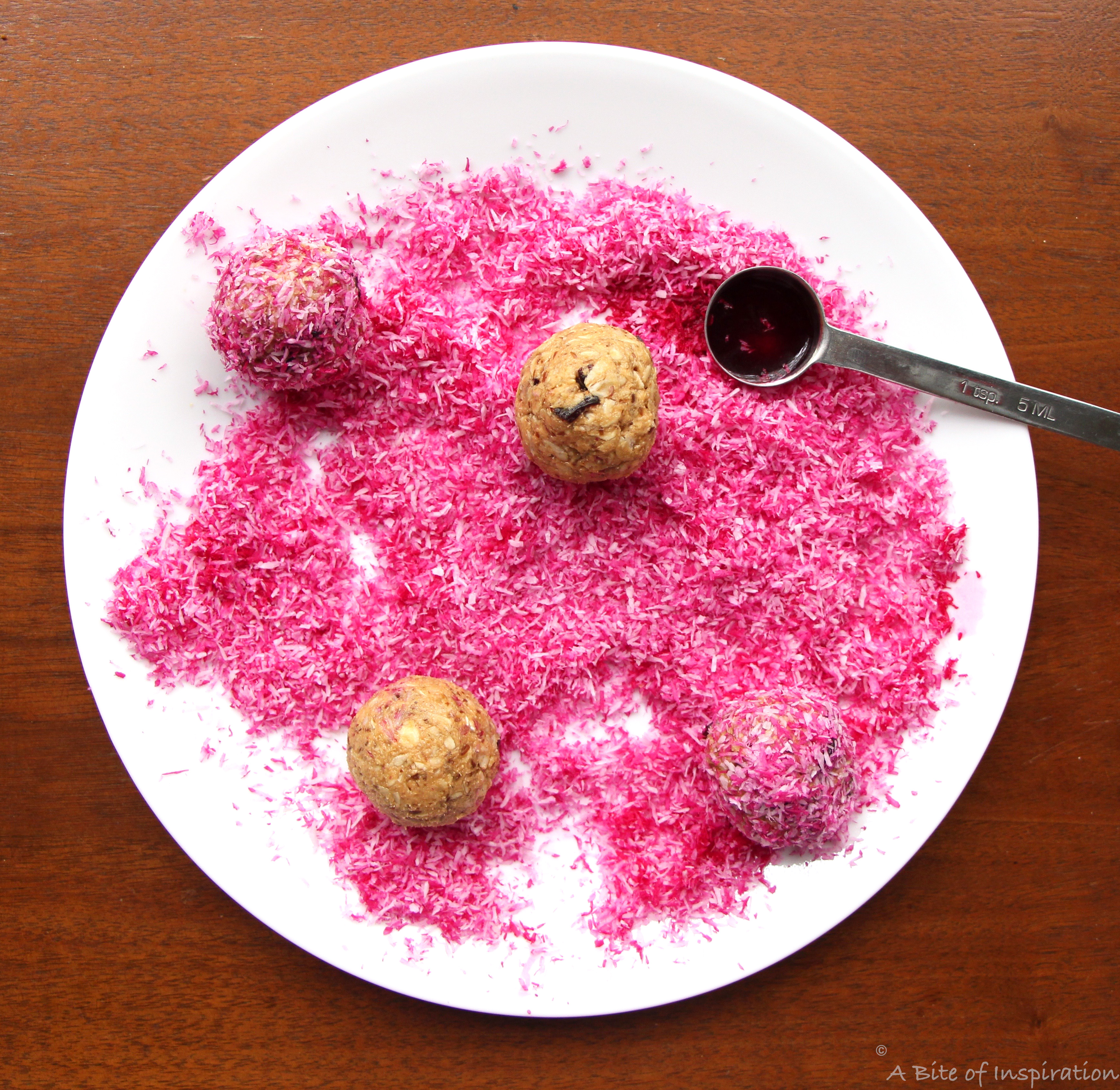 Protein snacks on a plate full of pink shredded coconut with a teaspoon of beet juice in the corner